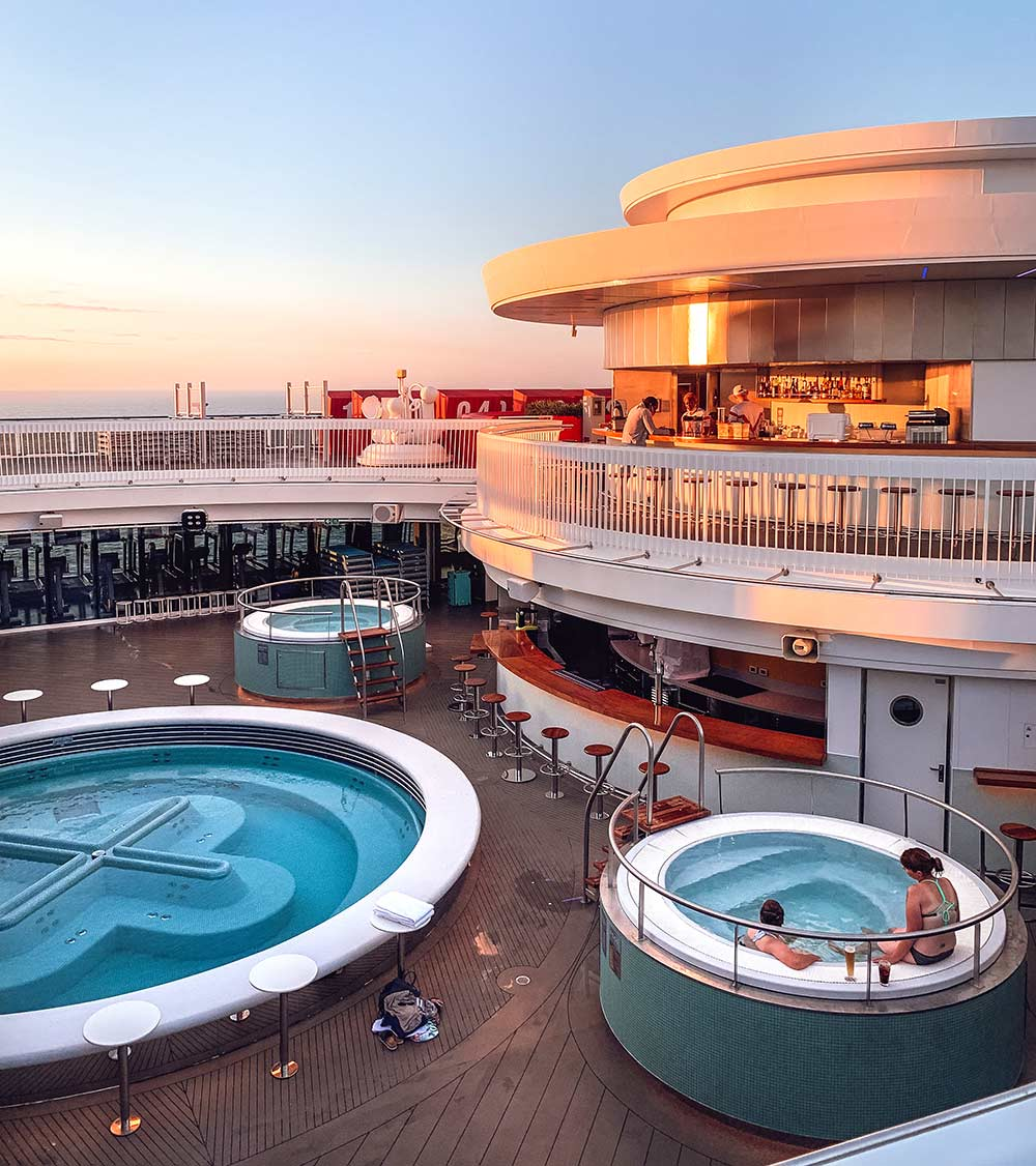 The outdoor heated pools and hot tubs onboard Virgin Voyages Scarlet Lady cruise ship