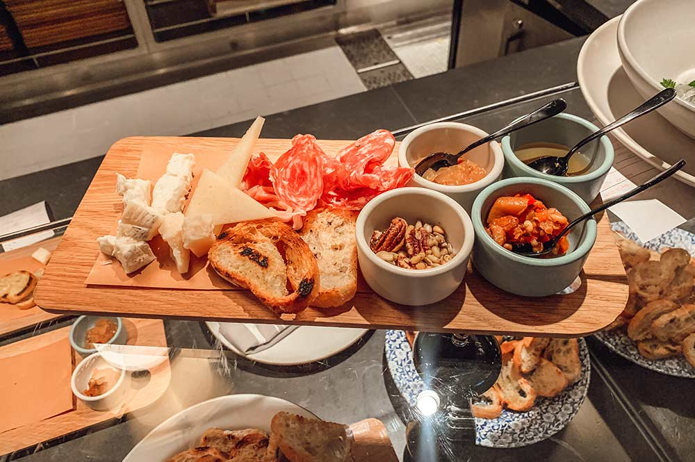 Cheese and charcuterie platter at Extra Virgin Italian restaurant onboard Virgin Voyages Scarlet Lady cruise ship