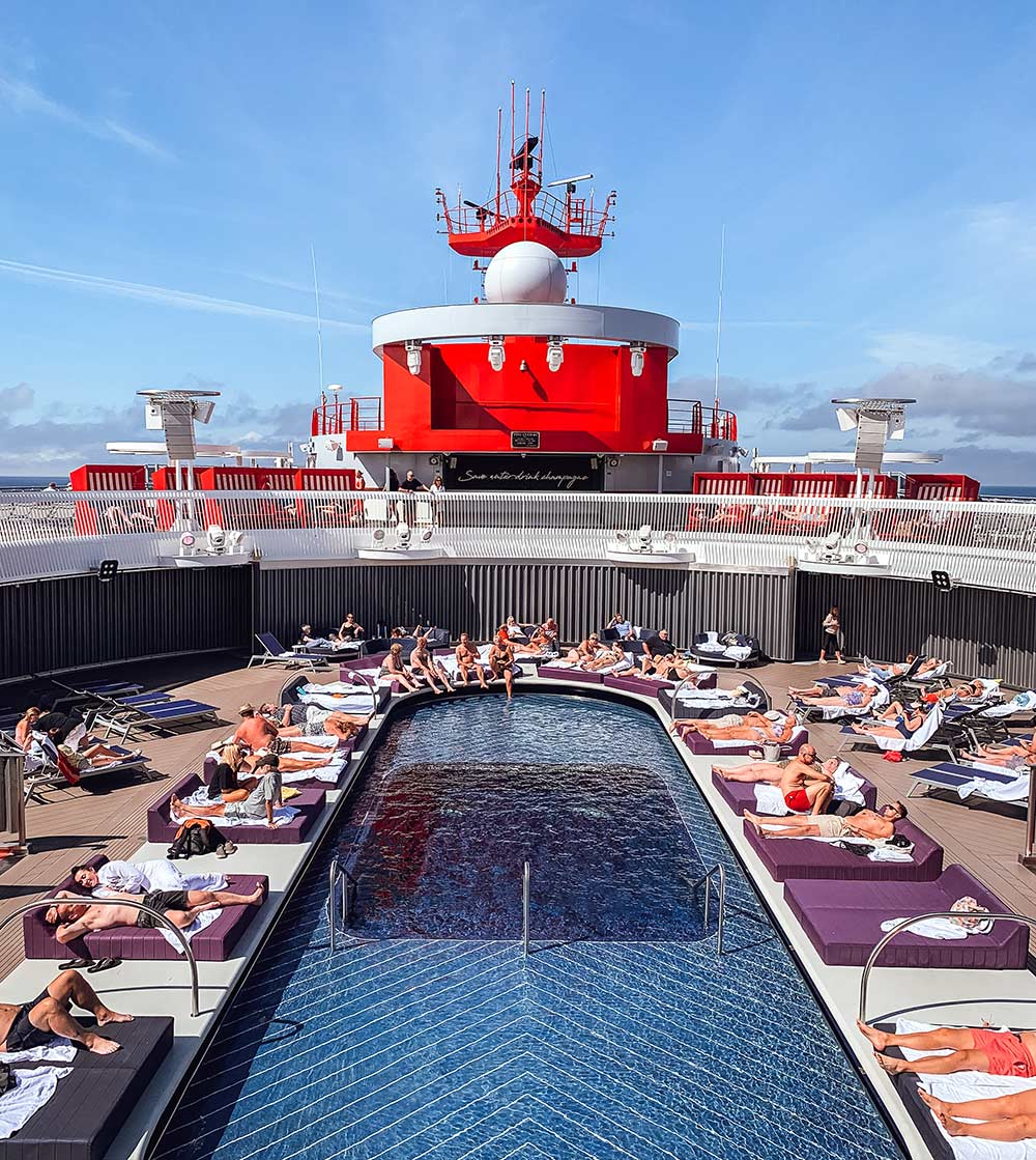 Outdoor pool onboard Virgin Voyages Scarlet Lady cruise ship